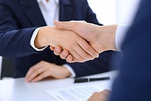 a banker shaking hands with a businessman who is looking to open up a Fairfax, VA CD account so that he can begin earning more money on interest