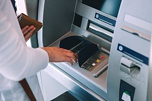 a business owner using an ATM to deposit money into her business money market account