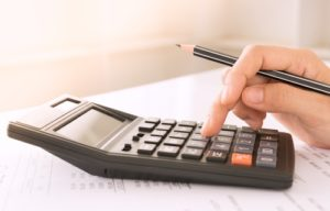 an investor using a calculator to determine how much his CD account would increase in interest over multiple years