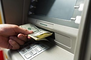 a man using an ATM which is part of his interest checking account plan