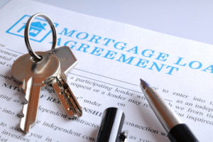 keys and a pen on top of a mortgage loan agreement for a business mortgage loan