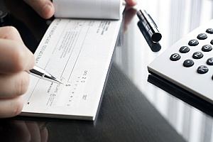 a check being written by a business owner who has positive pay services