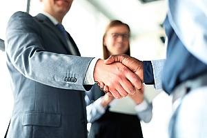 a small business owner shaking hands with a bank teller after opening a business banking account